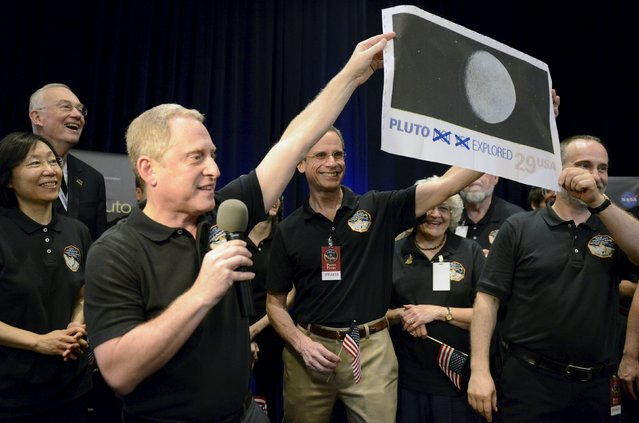 "NASA Principal Investigator for New Horizons mission Alan Stern (L) and Co-Investigator Will Grundy (R) hold up an enlarged, out-dated U.S. postage stamp with the ""NOT YET"" crossed out, during the celebration of the spacecraft New Horizons flyby of Pluto, at NASA's Johns Hopkins Applied Physics Laboratory in Laurel, Maryland, July 14, 2015. The flyby, which culminated after almost ten years of flight and over three billion miles, will allow New Horizons to photograph and collect data in the coming months. (Photo by Mike Theiler/Reuters)"