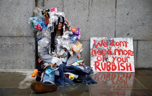 A demonstrator wearing an outfit made of rubbish sits outside the Houses of Parliament during the Extinction Rebellion protest in London, Britain, October 7, 2019. (Photo by Henry Nicholls/Reuters)
