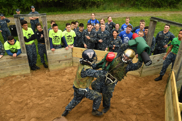 United States Naval Academy plebes, Jacob Burns, center, and Rocky Carroll face off in the pugil sticks portion of Sea Trials at the United States Naval Academy on Tuesday May 17, 2016 in Annapolis, MD. (Photo by Matt McClain/The Washington Post)