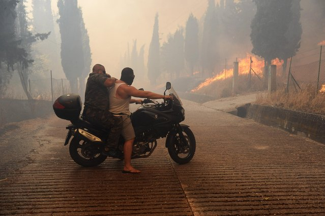Two men ride a motorcycle away from a fire in Athens on Friday, July 17, 2015. (Photo by Giorgos Bamboukos/InTime News via AP Photo)