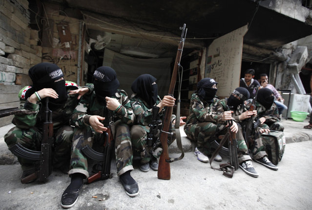 "Female members of the ""Mother Aisha"" battalion sit together along a street in Aleppo's Salaheddine district, September 19, 2013. (Photo by Loubna Mrie/Reuters)"