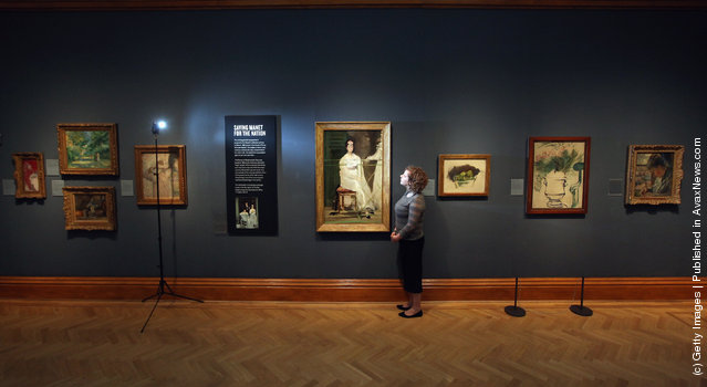A woman poses near a painting by Edouard Manet entitled 'Portrait of Mademoiselle Claus' from 1868 in the Ashmolean Museum