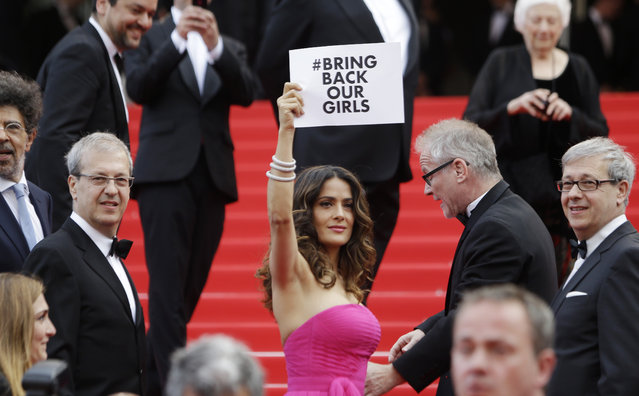 """Actress Salma Hayek holds up a sign reading """"bring back our girls"""", part of a campaign calling for the release of nearly 300 abducted Nigerian schoolgirls being held by Nigerian Islamic extremist group Boko Haram, as she arrives for the screening of Saint-Laurent at the 67th international film festival, Cannes, southern France, Saturday, May 17, 2014. (Photo by Thibault Camus/AP Photo)"""