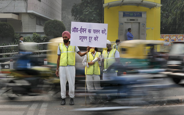 Volunteers wear pollution masks as they stand at a busy crossing with the banner saying obey odd and even, remove pollution, in New Delhi, India, Monday, November 4, 2019. (Photo by Manish Swarup/AP Photo)