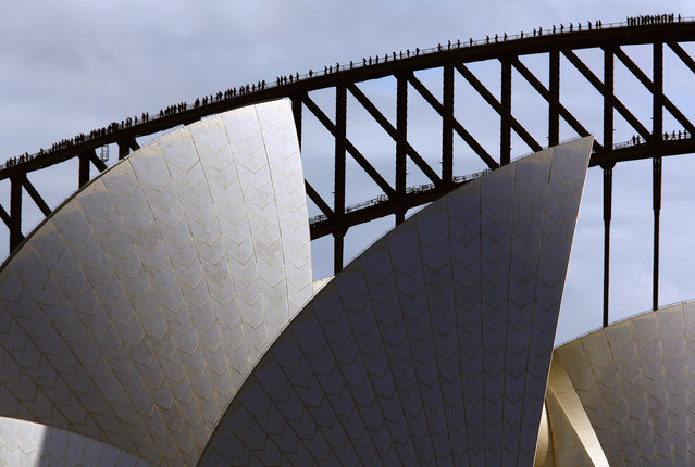 Climbers walk along the arch of the Sydney Harbour Bridge behind the Sydney Opera House on May 30, 2014 as they attempt to break the record for the most number of people on the arch of the famous bridge at the same time. The former record of 316 people, set in 2011, was broken when 340 people reached the top of the bridge on Friday during a charity event raising money for polio research. (Reuters/David Gray)