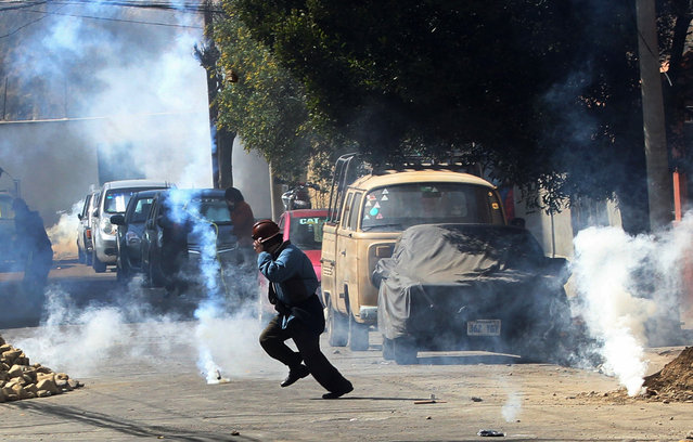 A miner from Bolivia's Potosi region runs from tear gas fired by police after the miners broke off dialogue with the government in La Paz, Bolivia, Wednesday, July 22, 2015. Residents in the capital city of Potosi have held a general strike for more than two weeks to pressure the national government to respond to their demands for a better hospital, an operable airport and a cement factory, among other things to revamp the economy. (Photo by Juan Karita/AP Photo)