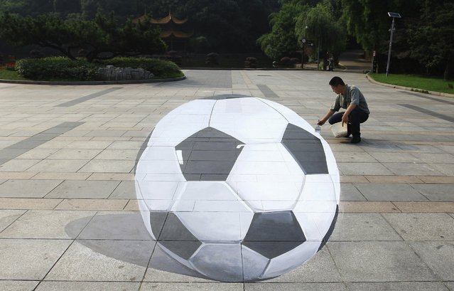 Artist He Haomin paints a 3-dimensional soccer ball at a park in Changsha, Hunan province, June 12, 2014. (Photo by Reuters/China Daily)
