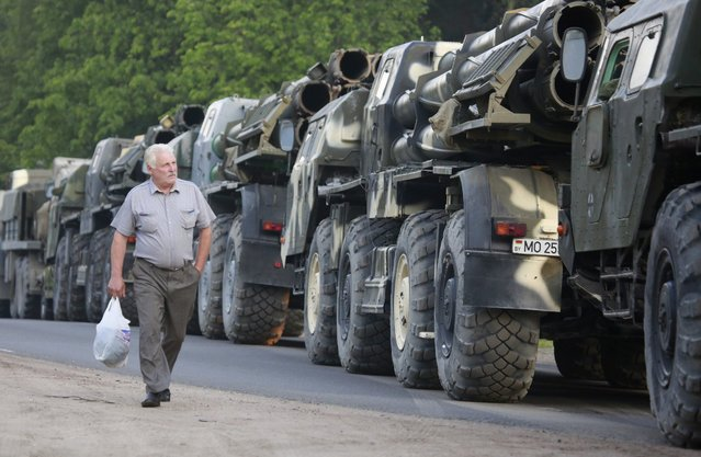 A man walks past a column of Belarus army armored personnel carrier (APC) vehicles during an Independence Day military parade rehearsal on the outskirts of Minsk, Belarus, 31 May 2016. The parade will take place on 03 July to mark the day of liberation of Belarusian territory from Nazi Germany's troops in 1944. (Photo by Tatyana Zenkovich/EPA)