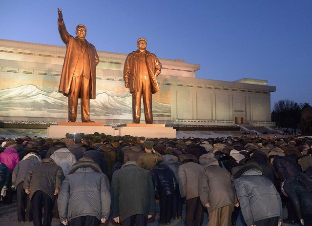 North Koreans bow to bronze statues of North Korea's late founder Kim Il Sung (L) and late leader Kim Jong Il at Mansudae in Pyongyang, in this picture taken on December 16, 2014 and provided by Kyodo December 17, 2014, to mark the third death anniversary of Kim Jong Il. (Photo by Reuters/Kyodo News)