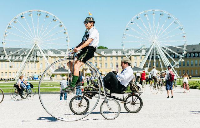 Participants dressed in historical clothing ride high-wheel bicycles during a bicycle ballet event at Schloss Karlsruhe palace during the 2017 International Veteran Cycle Association (IVCA) rally to celebrate the 200th anniversary of the bicycle on May 27, 2017 in Karlsruhe, Germany. Karl Drais, a German inventor, built and tested the first bicycle, called the Draisine, that ran without pedals in 1817. (Photo by Alexander Scheuber/Getty Images)