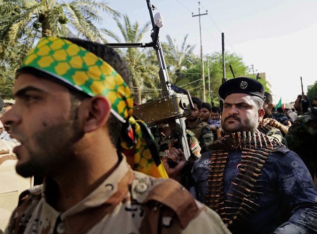 Shiite tribal fighters raise their weapons and chant slogans against the al-Qaida-inspired Islamic State of Iraq and the Levant (ISIL) in Basra, Iraq's second-largest city, 340 miles (550 kilometers) southeast of Baghdad, Iraq, Monday, June 16, 2014. Sunni militants captured a key northern Iraqi town along the highway to Syria early on Monday, compounding the woes of Iraq's Shiite-led government a week after it lost a vast swath of territory to the insurgents in the country's north. (Photo by Nabil Al-Jurani/AP Photo)