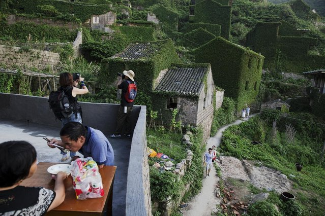 Tourists visit the abandoned fishing village of Houtouwan on the island of Shengshan as its former residents, now visiting, have lunch July 25, 2015. Xu Yueding and his wife Tang Yaxue, who left the village over 20 years ago, come back every day to their former house to welcome visiting tourists and sell them bottles of water, the only thing available to buy in the village. (Photo by Damir Sagolj/Reuters)