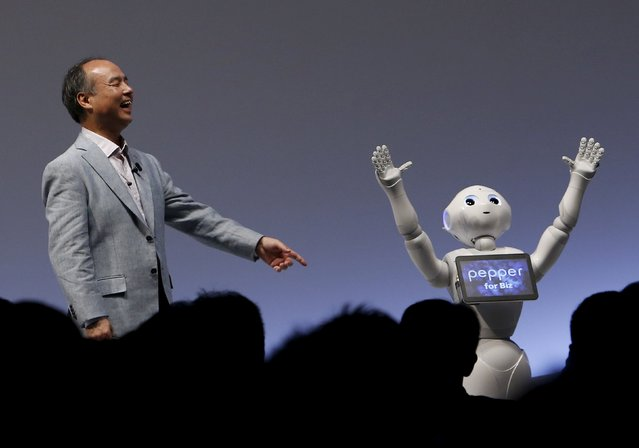 "SoftBank Group Corp. Chairman and CEO Masayoshi Son reacts as SoftBank's human-like robots named ""Pepper"" performs during the SoftBank World 2015 event in Tokyo, Japan, July 30, 2015. (Photo by Yuya Shino/Reuters)"