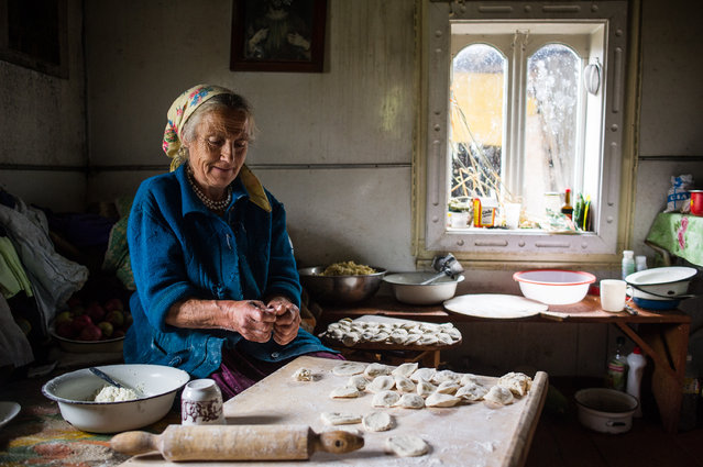 """""""Cooking varenyky for the family"""". Hutstul Vasylyna Semenyuk cooks varenyky (locally called """"pyrohy""""), a national Ukrainian and Hutstul meal, for her whole family in the summer kitchen in the mountains above Verkhovyna town, Ivano-Frankivsk region, Ukraine. Hustuls is an ethno-cultural group that for centuries lived in the Carpathian mountains, on the territory of Ukraine and northern Romania. Photo location: Verkhovyna, Ivano-Frankivsk region, Ukraine. (Photo and caption by Alex Furman/National Geographic Photo Contest)"""