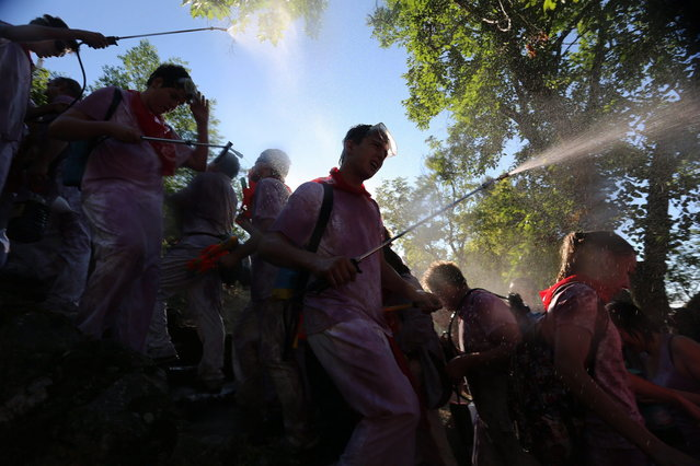 """Revelers spray wine on each other as they take part in the """"Battle of Wine"""" (La batalla del vino de Haro), a wine fight, during the Haro Wine Festival, in Haro, in the northern province of La Rioja on June 29, 2014. More than nine thousand locals and tourists threw around 130.000 litres of wine at each other during the Haro Wine Festival, according to local media. (Photo by Cesar Manso/AFP Photo)"""