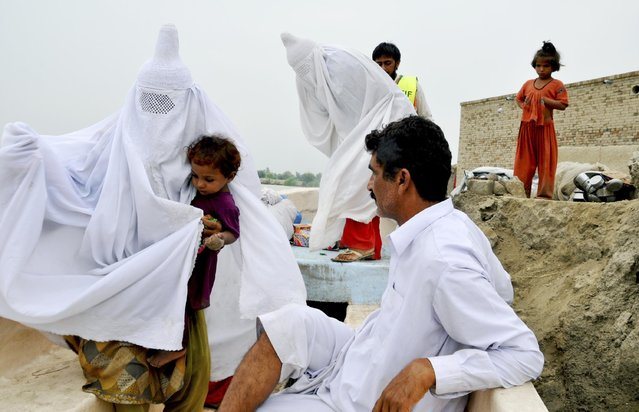 A Pakistani volunteer helps villagers out of a flooded area in Layyah, Pakistan, Wednesday, July 29, 2015. Floodwater inundated hundreds of villages, leaving tens of thousands of people homeless, authorities said. (Photo by Arif Ali/AP Photo)
