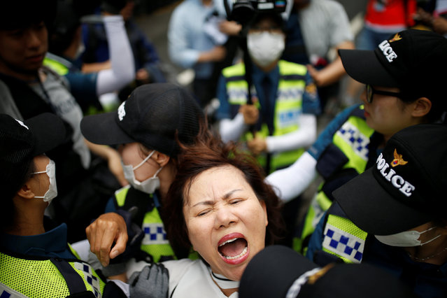 A Christian woman (C) who opposes homosexuality is detained as she tries to stop a march during the Korea Queer Culture Festival 2016 in central Seoul, South Korea, June 11, 2016. (Photo by Kim Hong-Ji/Reuters)