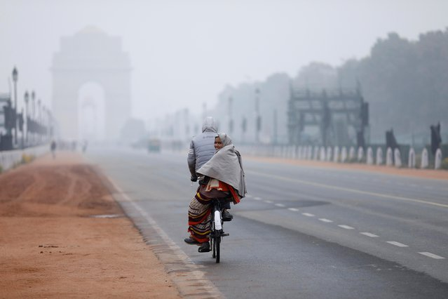 A woman sits behind a bicycle on a cold winter morning in New Delhi, December 31, 2019. (Photo by Anushree Fadnavis/Reuters)