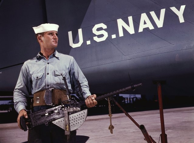A american non-com at the side machine gun of a huge YB-17 bomber is a man who knows his business and works hard at it. Photographed in May, 1942