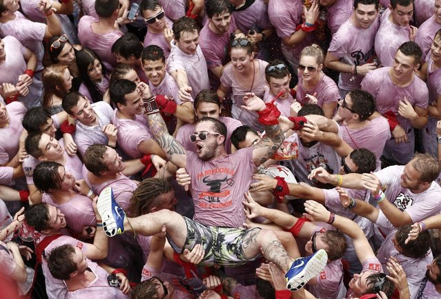 """Revelers in beverage stained white t-shirts celebrate just after the rocket fire or """"Txupinazo"""" marked the start of the Festival of San Fermin (or Sanfermines) in Pamplona, Spain, 06 July 2014. The annual nine day long running-with-the-bulls fiesta commemorates St. Fermin, Pamplona's patron saint. (Photo by Jesus Diges/EPA)"""
