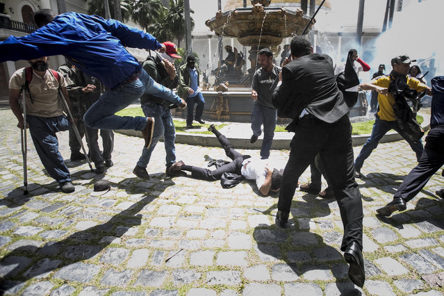 Deputy Armando Armas (C-on ground) is beaten by protesters at the National Assembly, in Caracas, Venezuela, 05 July 2017. A group of supporters of the Venezuelan government stormed the National Assembly (AN, Parliament) attacked and wounded some deputies who were in the enclosure for a session in commemorating the country's Independence Day. (Photo by Miguel Gutierrez/EPA)