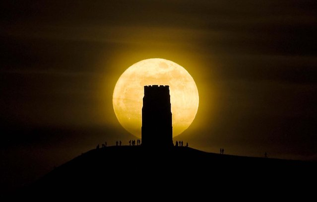 People stand beside St. Michael's Tower on Glastonbury Tor hill in England, watching the moon as it progresses across the sky at its closest point to the Earth in almost two decades