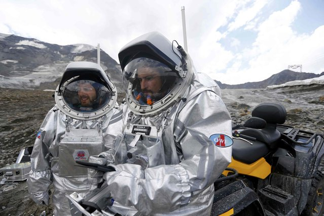 Stefan Dobrovolny of Austria and Inigo Munoz Elorza of Spain (R) stand in front of a quad bike during a simulated Mars mission on Tyrolean glaciers in Kaunertal, Austria, August 7, 2015. (Photo by Dominic Ebenbichler/Reuters)