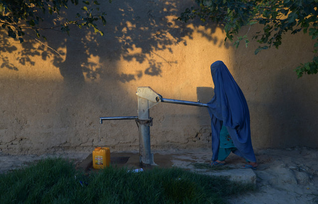 In this photograph taken on June 30, 2017 an Afghan woman collects water from a hand pump in Mazar-i-Sharif in Ghazni province. (Photo by Farshad Usyan/AFP Photo)
