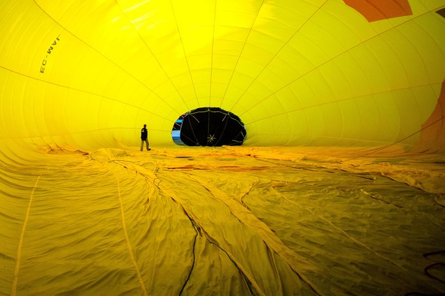 A hot air balloon is inflated at the European Balloon Festival in Igualada, Spain, on Jule 10, 2014. The early morning flight of over 30 balloons was shorter than expected due to windy weather. (Photo by David Ramos/Getty Images)