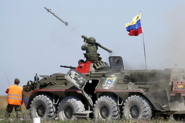 A serviceman from Venezuela fires an anti-aircraft missile with a Russian-made Igla ground-to-air launcher as he sits on top of an armoured personnel carrier (APC) during the Air defense battle masters competition as part of the International Army Games 2015 in the port town of Yeysk, Russia, August 9, 2015. (Photo by Maxim Zmeyev/Reuters)