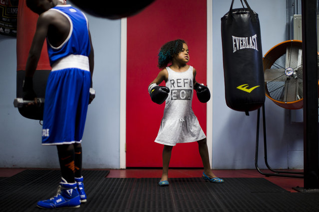 Kennedy Cunningham, 9, the daughter of boxer Steve Cunningham punches a bag as her father holds a media workout Wednesday, July 22, 2015, in Philadelphia. (Photo by Matt Rourke/AP Photo)