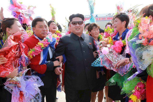 North Korean leader Kim Jong Un greets North Korea's female soccer team as they arrive at Pyongyang International Airport on Monday after winning the 2015 EAFF East Asian Cup, in this undated photo released by North Korea's Korean Central News Agency (KCNA) in Pyongyang on August 10, 2015. (Photo by Reuters/KCNA)
