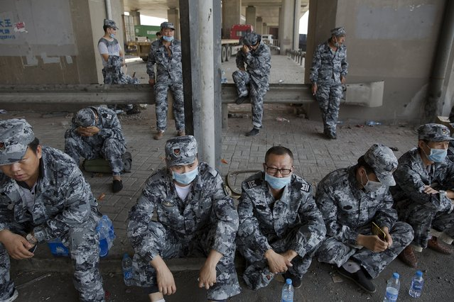 Soldiers rest under the bridge near the explosion site takes pictures of pluming smoke in Binhai new district in Tianjin, China August 13, 2015. (Photo by Damir Sagolj/Reuters)
