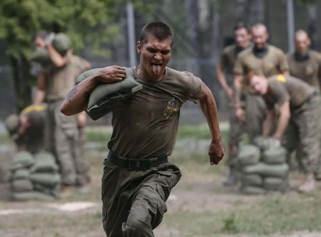 "A new volunteer for the Ukrainian interior ministry's ""Azov"" battalion takes part in tests before heading to frontlines in eastern Ukraine, at the battalion's training centre in Kiev, Ukraine, August 14, 2015. (Photo by Gleb Garanich/Reuters)"