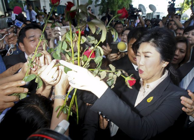 Ousted former Thai Prime Minister Yingluck Shinawatra receives red roses from supporters as she leaves the Supreme court in Bangkok, Thailand, May 19, 2015. (Photo by Chaiwat Subprasom/Reuters)