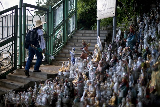 """A man walks past figurines at an """"idol cemetery"""" in Hong Kong, where thousands of small statuettes of deities and legends have been brought to overlook the sea, on July 19, 2014. Former owners of the figurines bring them to rest on a hill on the coast near a housing estate on Hong Kong island. The majority of religious followers in Hong Kong revolve around Chinese traditional religion, which is a mixture of Buddhism, Taoism and Confucianism, along with local practices and beliefs. (Photo by Alex Ogle/AFP Photo)"""