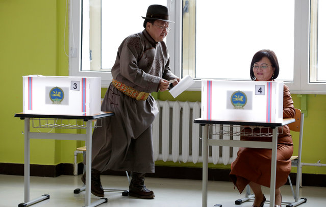 Mongolian President Tsakhiagiin Elbegdorj  (L) and his wife Bolormaa Khajidsuren attend voting for the parliamentary elections at a polling station in Ulaanbaatar, Mongolia, June 29, 2016. (Photo by Jason Lee/Reuters)