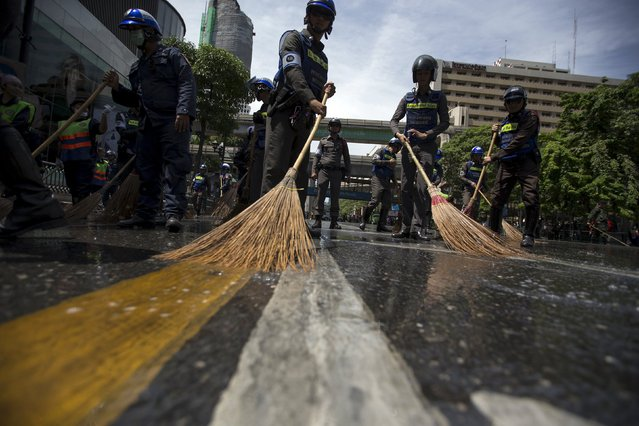 Police officers clean a street near the site of a deadly blast in central Bangkok, Thailand, August 18, 2015. (Photo by Athit Perawongmetha/Reuters)