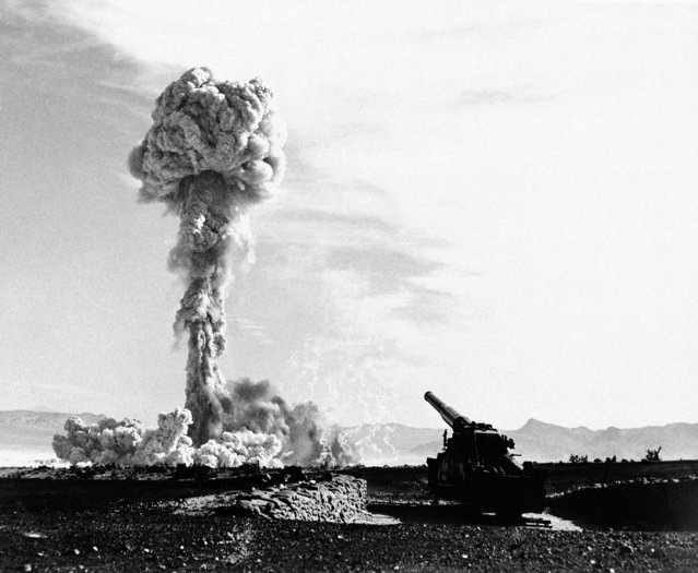 The towering lacy mushroom from the atomic cannon's first test rises from desert floor at Frenchman's flat, near Las Vegas, Nevada on May 25, 1953. The 280-mm gun which tossed the shell to its destination six or seven mile away is in the foreground. The rifle was touched off electrically, with the gun-loading crew entrenched a safe distance away. This picture, released on May 27, by the air force, was made probably about 10 seconds after the explosion. (Photo by AP Photo)