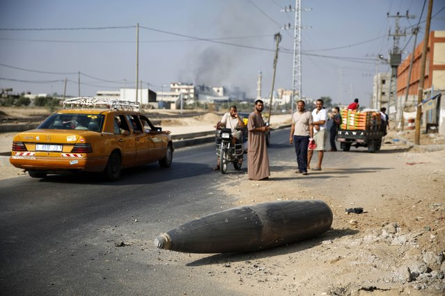 Palestinians look at an unexploded Israeli shell that landed on the main road outside the town of Deir Al-Balah in the central Gaza Strip August 1, 2014. Israeli shelling near the southern Gaza town of Rafah killed at least 40 people on Friday, the local hospital said, as a ceasefire that went into effect only hours earlier crumbled. Israel accused Hamas and other Palestinian militant groups of violating the U.S.– and U.N.-mediated truce, but did not elaborate, amid Israeli media reports that gunmen had fired at Israeli soldiers in the Rafah area. (Photo by Finbarr O'Reilly/Reuters)