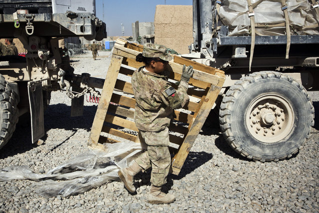 Specialist Joanne Read, of the U.S. Army's Bravo Company, 1st Battalion, 36th Infantry Regiment, First Armored Division, helps unload a resupply truck at Command Outpost AJK in Maiwand District, Kandahar Province, Afghanistan, January 24, 2013. (Photo by Andrew Burton/Reuters)