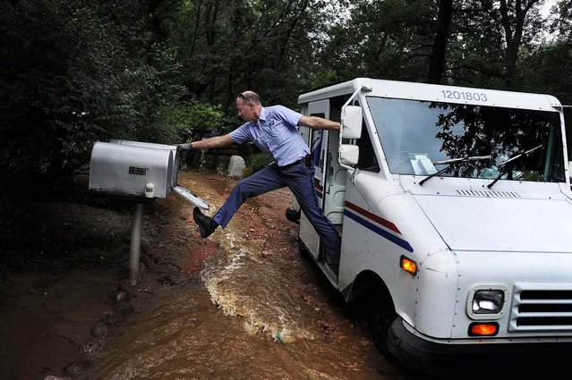 Honorable Mention, Feature. Photo by Michael Ciaglo:  Dave Jackson closes a mailbox with his foot after delivering the mail to a home surrounded on three sides by a flooded Cheyenne Creek in Colorado Springs. (Photo by Michael Ciaglo)