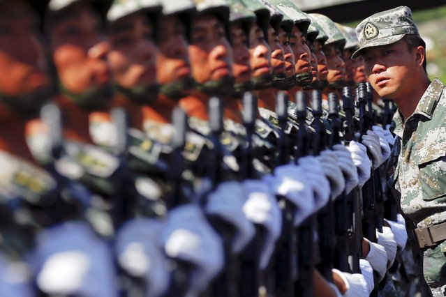 An officer gives instructions as soldiers of China's People's Liberation Army form a line during a training session for a military parade to mark the 70th anniversary of the end of World War Two, at a military base in Beijing, China, August 22, 2015. (Photo by Damir Sagolj/Reuters)