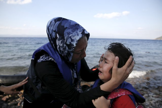 An Afghan mother comforts her crying child moments after a dinghy carrying Afghan migrants arrived on the island of Lesbos, Greece August 23, 2015. Greece, mired in its worst economic crisis in generations, has been found largely unprepared for a mass influx of refugees, mainly Syrians. Arrivals have exceeded 160,000 this year, three times as high as in 2014. (Photo by Alkis Konstantinidis/Reuters)