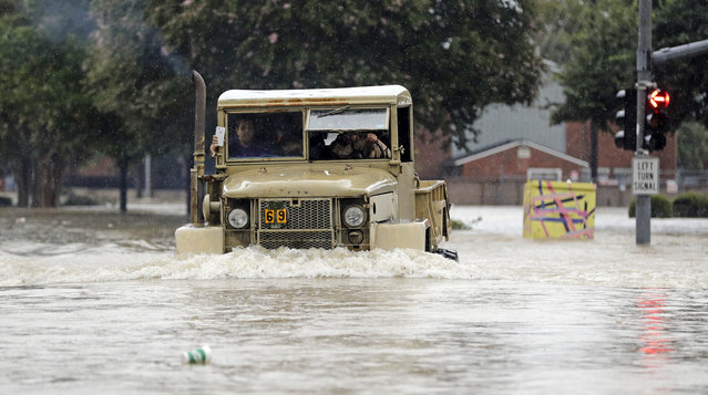 A truck pushes through floodwaters from Tropical Storm Harvey on Sunday, August 27, 2017, in Houston, Texas. (Photo by David J. Phillip/AP Photo)