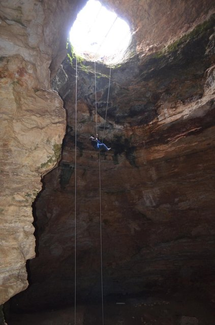 Justin Sipla ascends a rope 80 feet to reach the mouth of Natural Trap Cave in north-central Wyoming after working on the cave's floor in this July 2014 image. The cave holds the remains of tens of thousands of animals, including many now-extinct species, from the late Pleistocene period, tens of thousands of years ago. Scientists have resumed digging here for the first time in more than 30 years. (Photo by AP Photo/Bureau of Land Management)