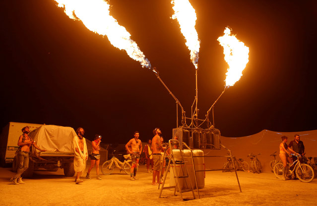 Participants interact with a fire installation as approximately 70,000 people from all over the world gathered for the annual Burning Man arts and music festival in the Black Rock Desert of Nevada, U.S. on  on August 31, 2017. (Photo by Jim Urquhart/Reuters)