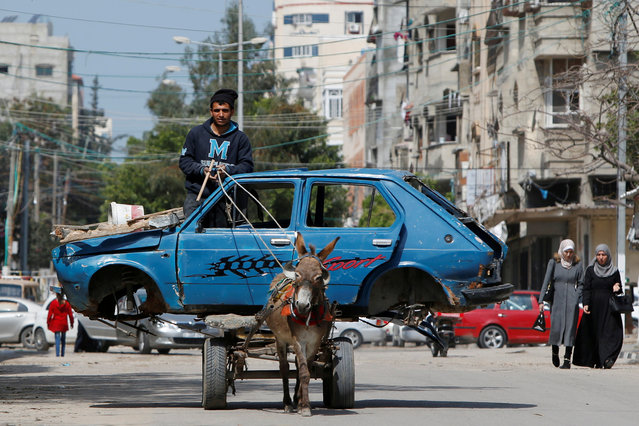 A Palestinian man rides a donkey-drawn cart transporting an old car to a scrap yard, in Gaza City on March 15, 2020. (Photo by Mohammed Salem/Reuters)
