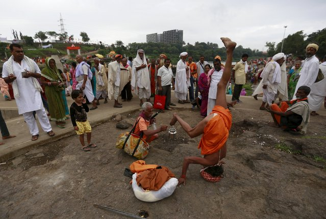 A sadhu, or a Hindu holy man, stands on his head as he receives alms from a devotee on the banks of Godavari river during Kumbh Mela or the Pitcher Festival in Nashik, India, August 28, 2015. (Photo by Danish Siddiqui/Reuters)