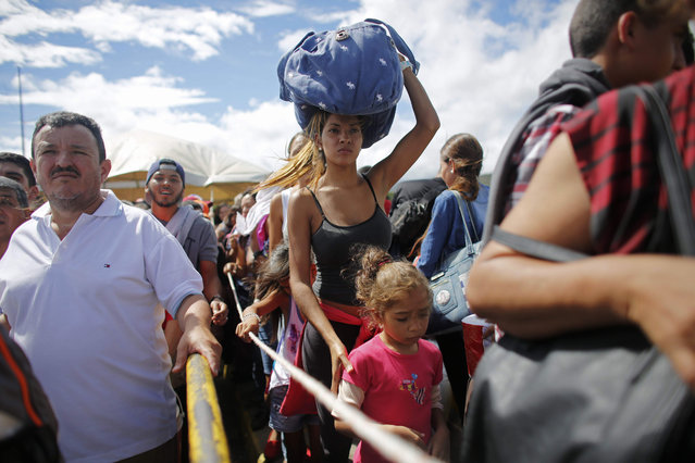 A woman carrying a bundle on her head wait in line to cross the border into Colombia through the Simon Bolivar bridge in San Antonio del Tachira, Venezuela, Sunday, July 17, 2016. Tens of thousands of Venezuelans crossed the border into Colombia on Sunday to hunt for food and medicine that are in short supply at home. It's the second weekend in a row that Venezuela's government has opened the long-closed border connecting Venezuela to Colombia. (Photo by Ariana Cubillos/AP Photo)